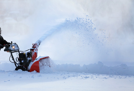 man working with snow blower after winter storm in city