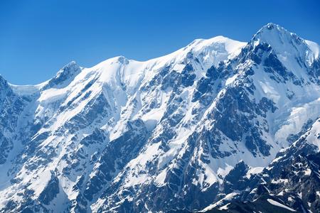Cumbre de la montaña bajo la nieve. Paisaje de invierno en día soleado frío. cielo azul por encima de un pico