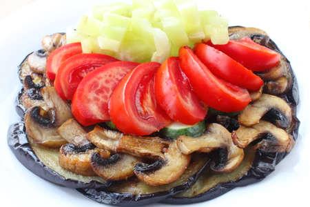 Berenjenas fritas y champiñones con tomates frescos, pepinos y pimientos en un plato blanco Foto de archivo - 11011544