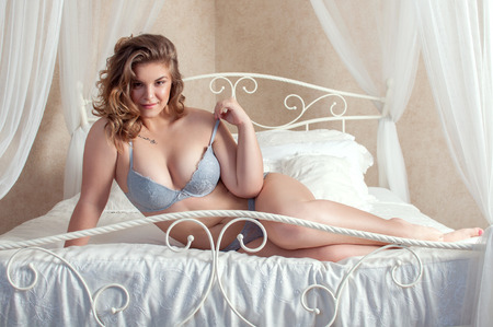 to size: plus size female on bed Stock Photo