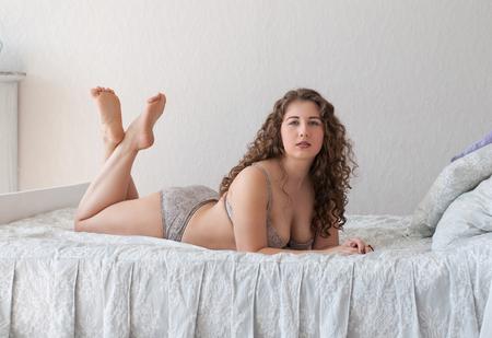 belles jambes: chubby femme aux pieds nus adorable en lingerie couché sur les pieds de lit traversé Banque d'images