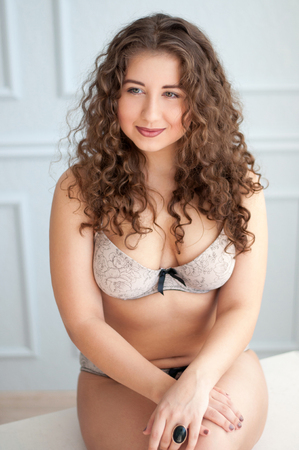 boudoir: Boudoir portrait a chubby curly smiling female in lingerie