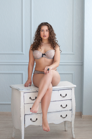 sit: plus size sexy curly model in lingerie sitting on white chest of drawers