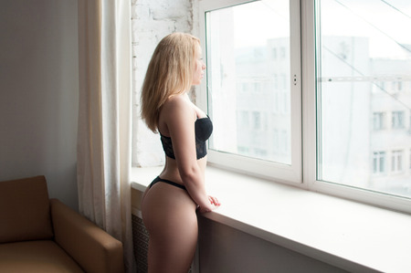 plump: plump blonde in corset and panties standing at the window with his hands on the windowsill Stock Photo