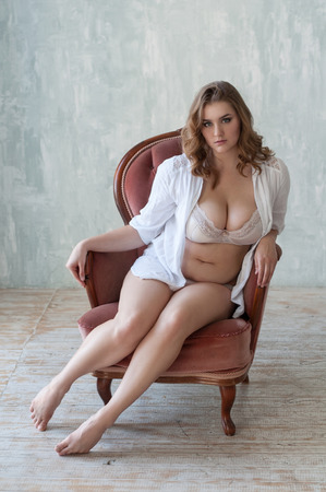 plus size girl in white lingerie sitting on the vintage coral armchair Stock Photo