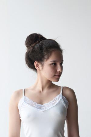 Ragazza di volto carino con fasce di acconciatura guardare al lato su sfondo bianco Archivio Fotografico - 82244323