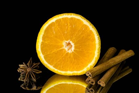 Slice of orange and cinnamon and star anise on black background photo