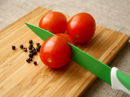 pepe nero: tomatoes with black pepper on the board with knife