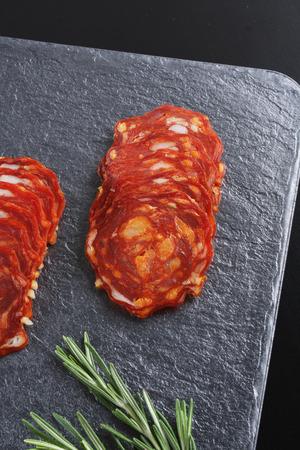spicy Spanish pork sausage slicing on a dark stone background