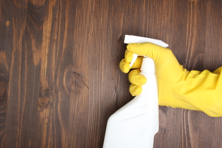 yellow glove and a white bottle sprayer on a wooden background