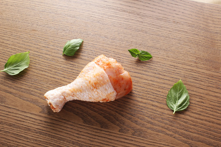 Chicken drumstick in marinade on a wooden background
