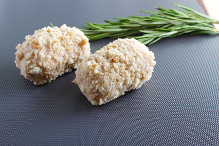 chicken cutlet roll in breading cooking on a gray background
