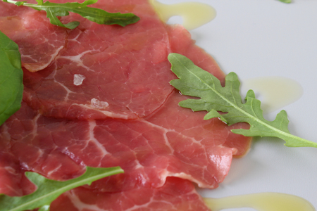 beef carpaccio on a light gray basil background