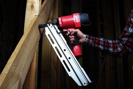 red pneumatic nails nailing hand gun