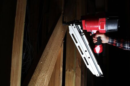 red pneumatic nails nailing hand gun