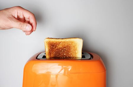 hand toast and orange toaster on a light background