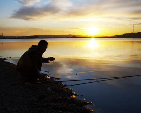 fisher fasten the bait on the sunset photo