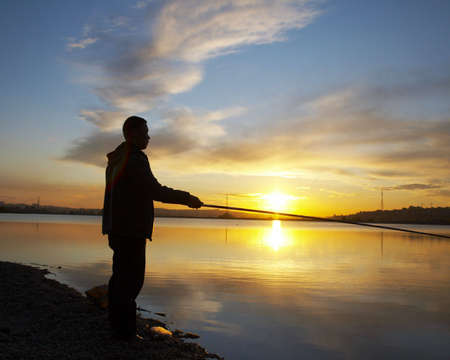 fishingline: man with fishing rod on the sunset