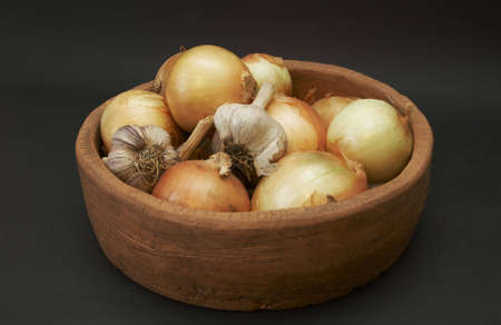 onion and garlic bulbs lying in the ceramic dish photo