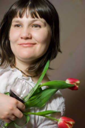 middle-aged woman with tulips and glass of wine. Happy expression, very emotional photo