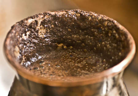 cezve: close-up of copper cezve with boiled over black coffee Stock Photo