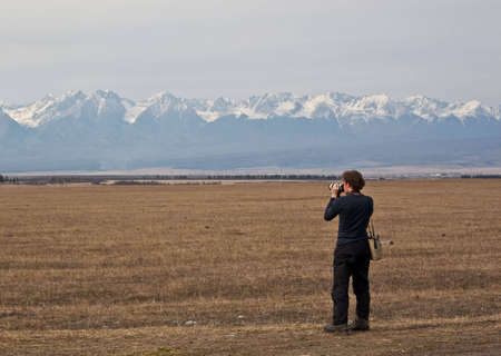distant work: photo of photographer taking a photograph of distant mountains Stock Photo