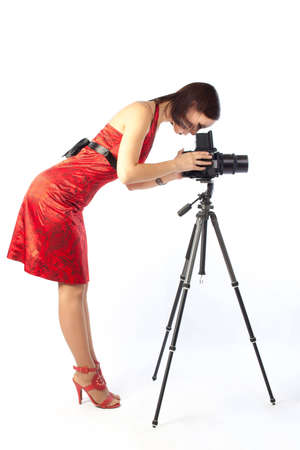 photo of beautiful girl in red dress working with big camera mounted on tripod. Isolation on the white Stock Photo - 6338314