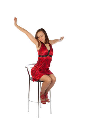 photo of beautiful girl in red dress sitting on the chair and stretching oneself. Isolation on the white photo