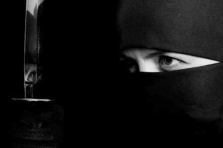 sabotage: Photo of woman in ninja suit with wakizashi on black background. BW photo Stock Photo