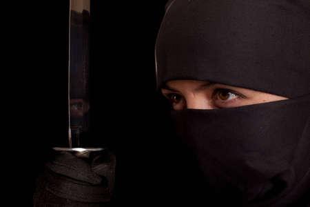 Photo of woman in ninja suit with wakizashi on black background