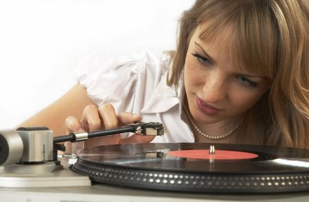 The girl listens to a phonograph record