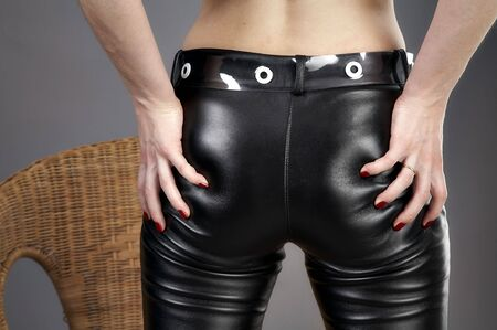 Female fingers on leather trousers Stock Photo