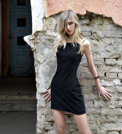 The girl the blonde in a black dress on a background of a brick wall Stock Photo - 4118107