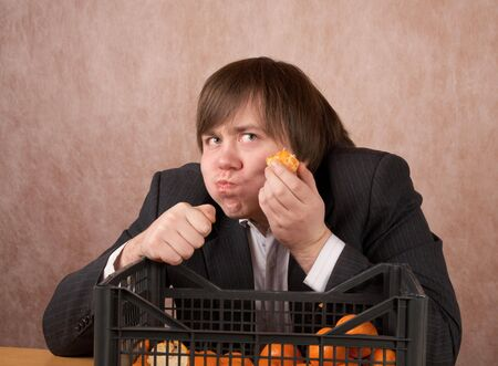 The young man eats tangerines from a box photo