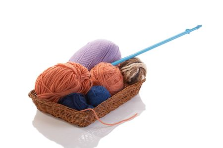 Knitting spokes with ball of wool in  basket on white background photo