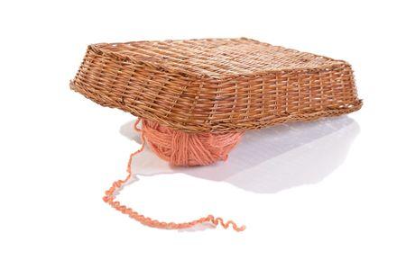 Ball of  wool under  basket on  white background photo
