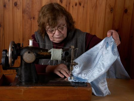 The old woman sews on the sewing machine photo
