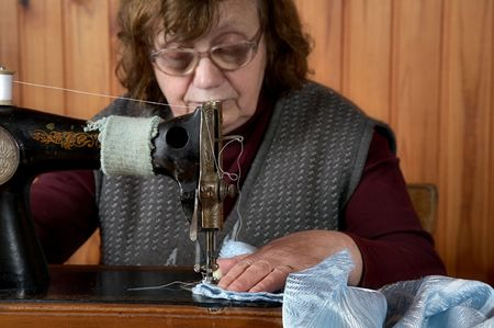 The old woman sews on the sewing machine Stock Photo