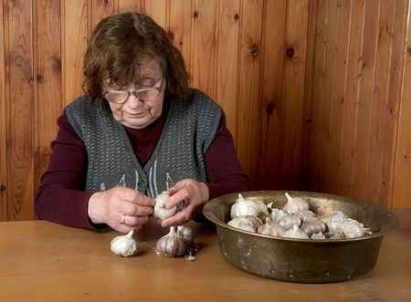 The old woman touches garlic sitting for a table
