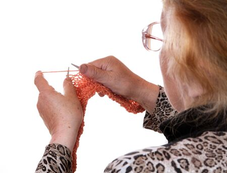 The old woman is engaged in knitting on a white background