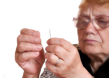 The old woman passes  thread in needle on  white background