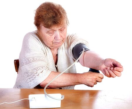 The old woman measures arterial pressure upon a white background