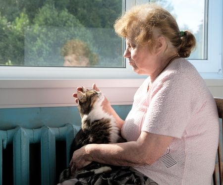 The old woman caress cat sitting at a window