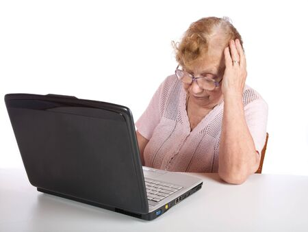 The old woman in glasses looks at the screen notebook on a white background photo