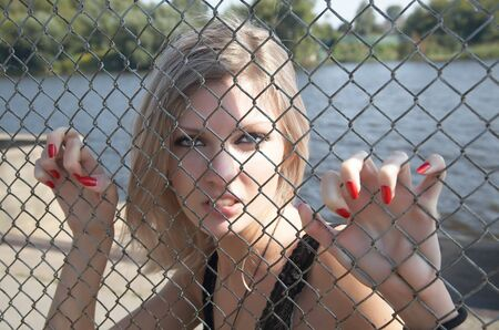 seized: The girl has spitefully seized hands an iron grid Stock Photo