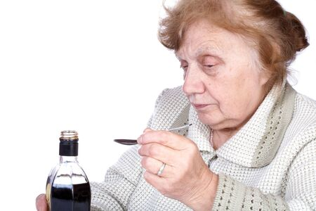 octogenarian: The old woman pours a liquid in the spoon Stock Photo