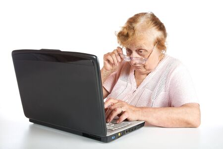 The old woman in glasses looks at the screen notebook on a white background