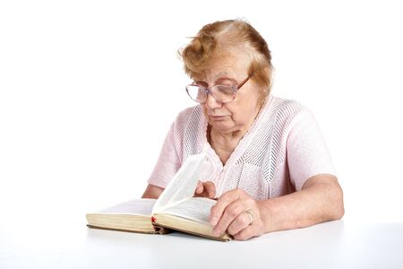 old woman in glasses reads the book on a white background photo