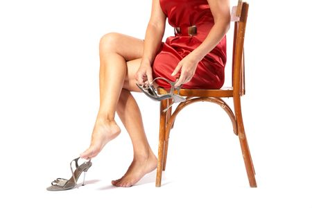 The woman puts shoes sitting a chair on white background Stock Photo