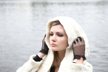 The thoughtful girl in  knitted dress on a background of water Stock Photo - 6713168